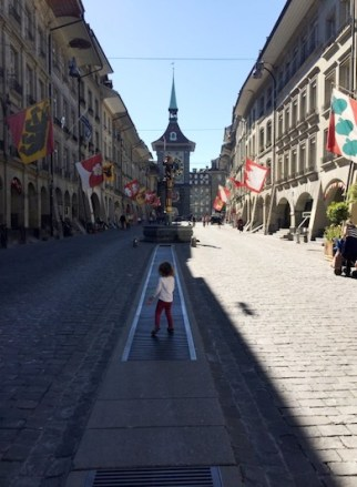 Little girl strolling down the Kramgasse towards one of many fountains in Bern, with flags all along her path