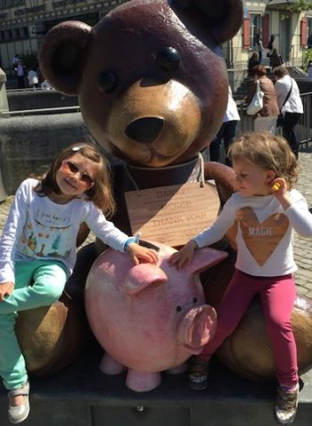 CosmopoliClan's two little girls, a bear statue and a piggy bank at the The Bärengraben, or Bear Pit, in Bern