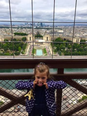 Little girl making silly faces from the Eiffel tower in Paris wit a view of the Jardins du Trocadéro