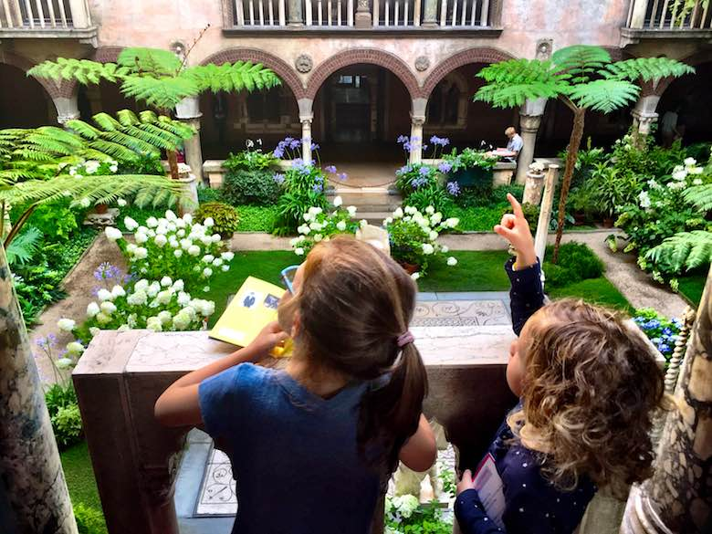 Two little girls standing on the balcony of the Isabella Stewart Gardner museum in Boston, overlooking the stunningly green courtyard