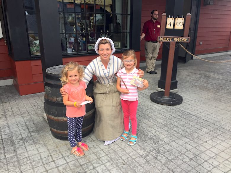 Two little girls posing with a costumed historic figure in front of the Boston Tea Party Museum
