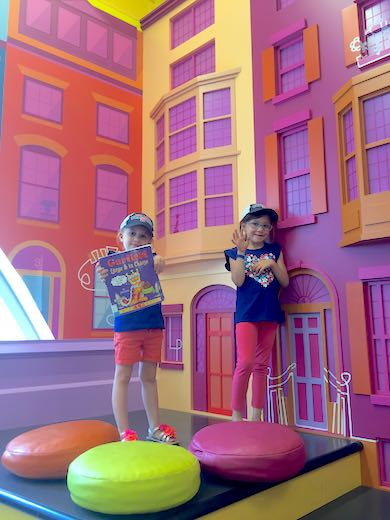 Two girls, one showing a book and the other waving, against the bright purple facade of the house-shaped reading corner in Boston Public Library