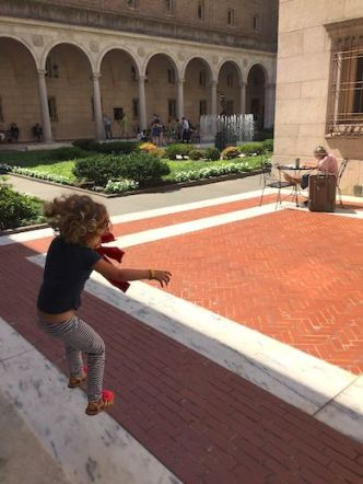 Little girl jumping from the stairs in the courtyard of the Boston Public Library