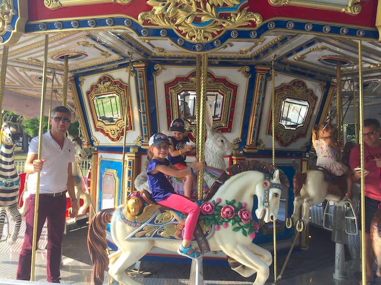 Two girls and their dad on the carousel in Boston Common