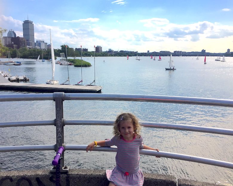 Little girls posing near the Charles River Esplanade, with the sailing boats in the background