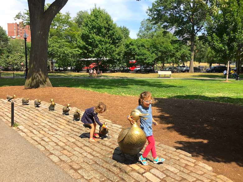 """The CosmopoliClan sisters playing around the """"Make way for ducklings' statue in Boston's Public Garden"""
