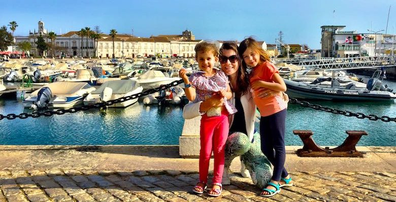 Mother and her 2 little girls posing at the marina of Faro in authentic Algarve in Portugal