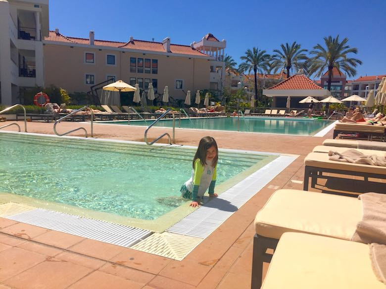 A girl posing at the pool of the Hilton Vilamoura As Cascatas Golf Resort & Spa in authentic Algarve in Portugal
