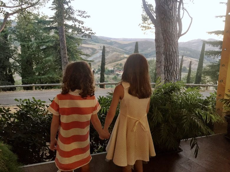 Two sisters wearing dresses and holding hands while admiring the mountain view from the restaurant terrace at Palazzo di Varignana Resort & Spa near Bologna
