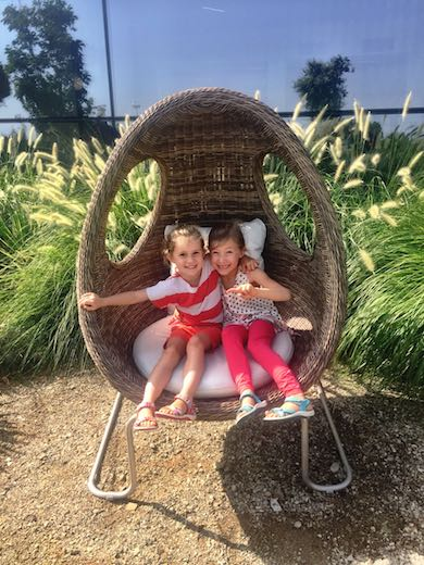 Two sisters relaxing and smiling in a wicker chair