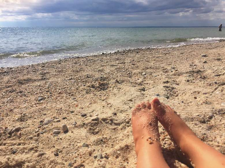 Two children's feet, covered in sand and pointing towards the ocean in Cape Cod