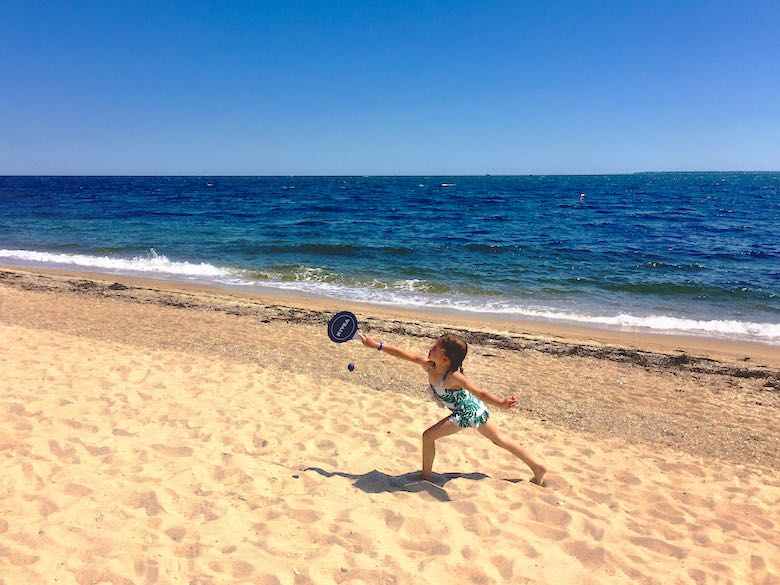 A little girl playing ping pong on a beach in Cape Cod, striking a pose to hit the little ball