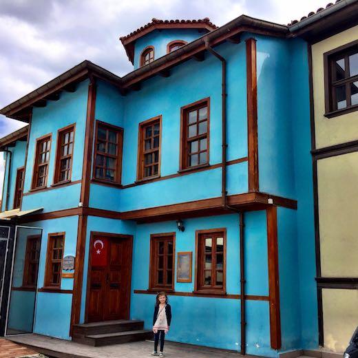 Little girl posing in front of a blue konak in in colorful Odunpazarı, the historic district of Turkish Eskişehir