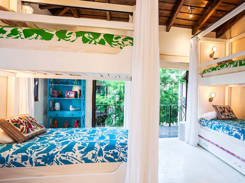Two bunk beds with bright bedding in a room with tropical setting in Case Brewer in Costa Rica, available via Luxury Retreats