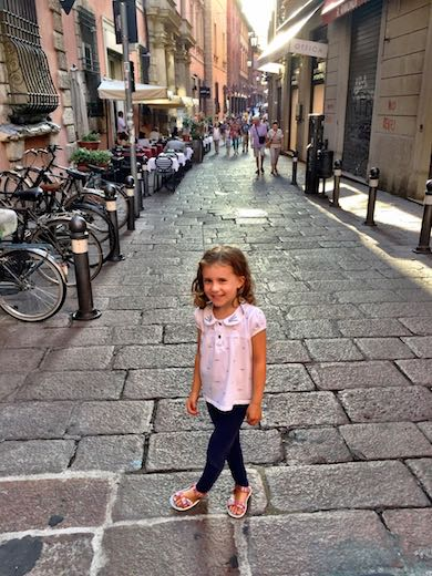 Little girl posing in Via Clavature in Bologna
