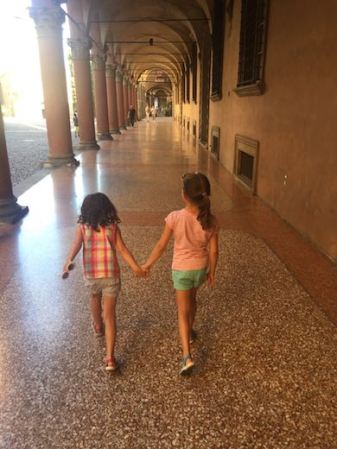 Two little girls holding hands while walking in one of the porticos in Bologna, Italy