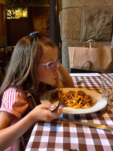 Little girl enjoying a typical tagliatelle al ragu or pasta bolognese in Bologna