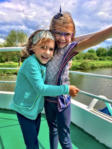 Two sisters cuddling on the deck of a boat while cruising the Moselle river during a family trip to Luxemburg with kids