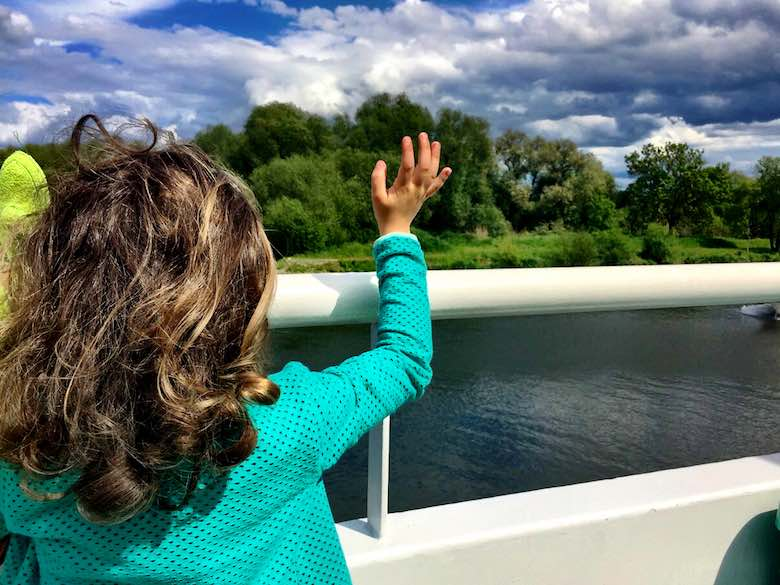 Rear view of a little girl in green cardigan waving to another boat when cruising the Moselle river in Luxemburg