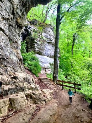 A little girl passing a large rock formation on a hiking trail in the Mullerthal during a visit to Luxemburg with kids
