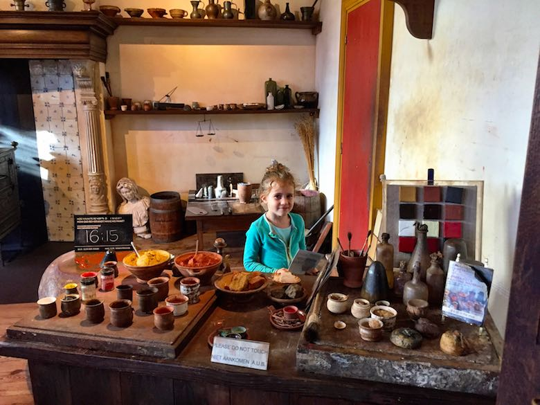 Little girl admiring all the pigments Rembradt used to use to create his oil paint in the Rembrandt House in Amsterdam