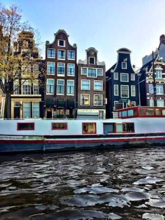 Amsterdam's dancing houses seen from the water, with a house boat in the center of the photo