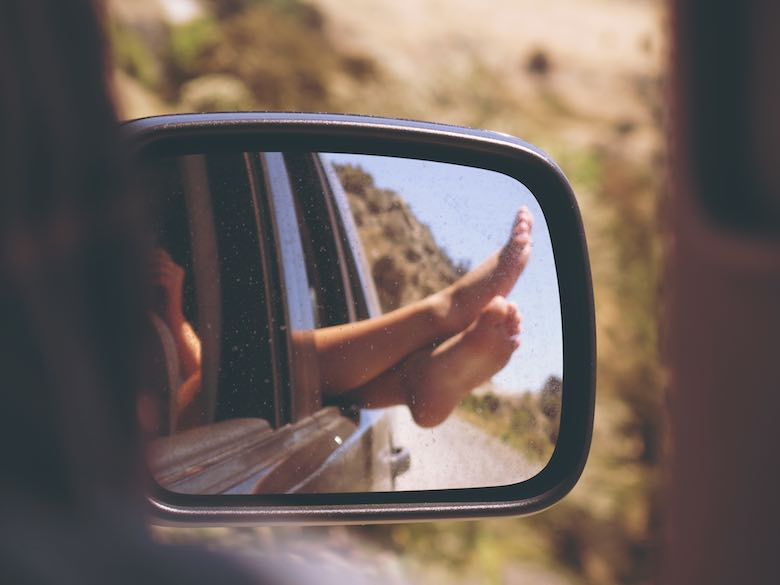 Rearview mirror showing two feet hanging out of the car window during a roadtrip