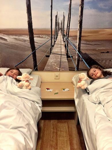 Twee meisjes in hun bed tonen hun schaapje, het symbool van Texel