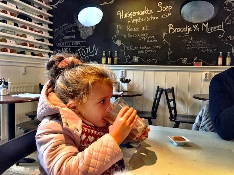 Een meisje in roze jas drinkt een warme chocolademelk in een hippe eetgelegenheid op Texel, op de achtergrond staat het menu met krijt op de zwarte muur geschreven