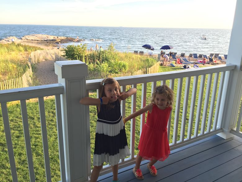 Two sisters in a fancy dress, one making silly faces, on the porch of the Curio by Hilton Madison Beach Resort, a family-friendly luxury hotel in Connecticut