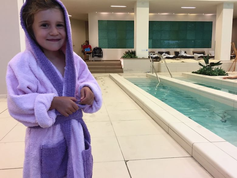 A little girl wearing a bathrobe at the spa of the Palazzo di Varignana Resort & Spa, one of Italy's prime family-friendly luxury hotels