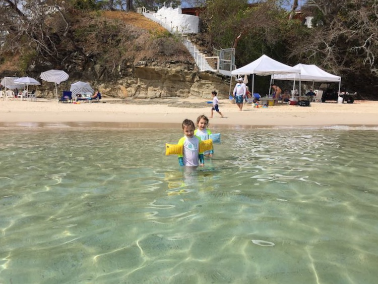 Two sisters in the shallow waters of Isla Contadora, the ultimate one-day beach getaway from Panama City, picture taken from the water with a view of the beach