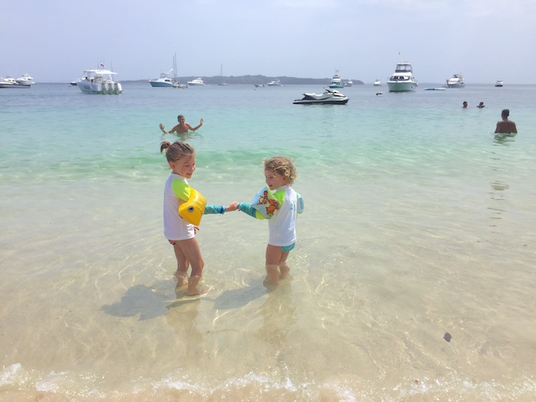 Two sisters holding hands in the shallow waters of Isla Contadora, the ultimate one-day beach getaway from Panama City