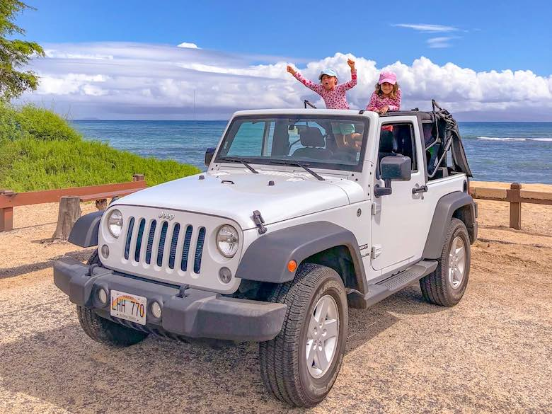 Two little sisters cheering through the roof of our Jeep Wrangler, a road trip is one of the things to do in Maui with kids