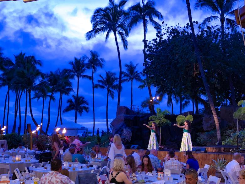 One of the most memorable things to do in Maui with kids is attending a Maui luau, dancers on stage against a nightly sky