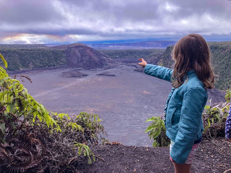 Little girl wearing a green jacket and looking out over the Kilauea Iki crater and pointing at the fumes coming from the Halema'uma'u crater in Hawaii Volcanoes National Park