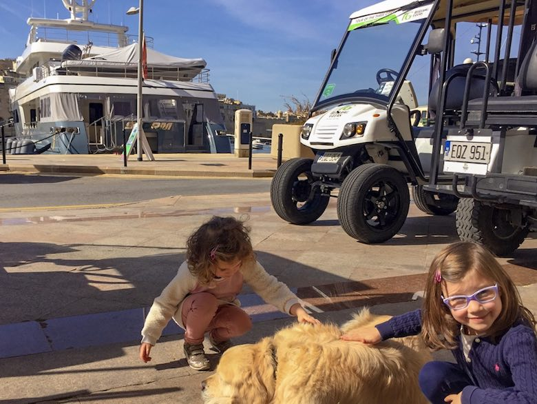 Two little girls sociazising with the dog at the Rolling Geeks office in Vittoriosa or Birgu