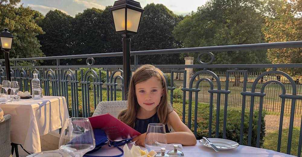 Little girl at the dinner table on the terrace of the La Véranda by Gordon Ramsey restaurant at the Waldorf Astoria Trianon Palace Versailles