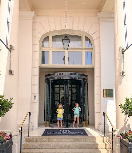 Two little girls in front of the entrance of the Little girl exploring the garden of the Waldorf Astoria Trianon Palace Versailles