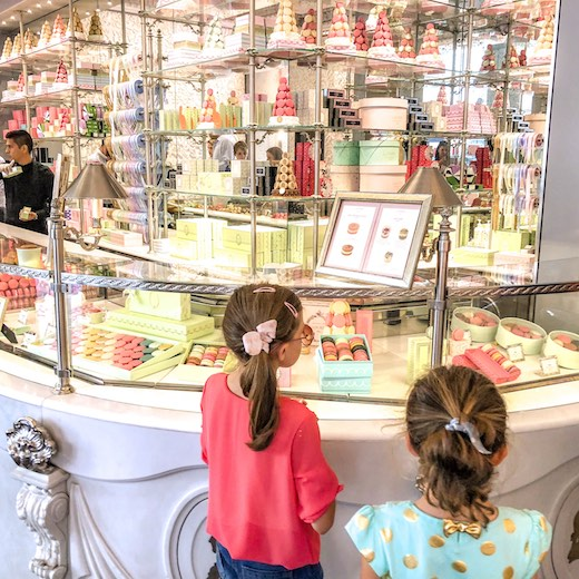 Two little girls mouthwatering at the macarons at Laduree in Paris