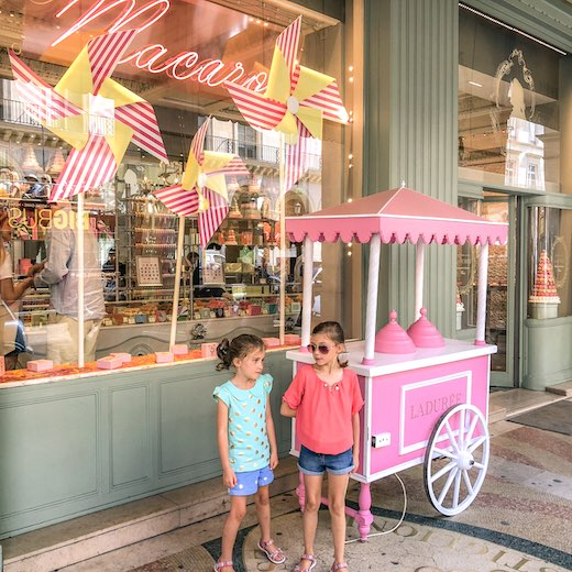 Two little girls waiting in front of a Laduree store in Paris