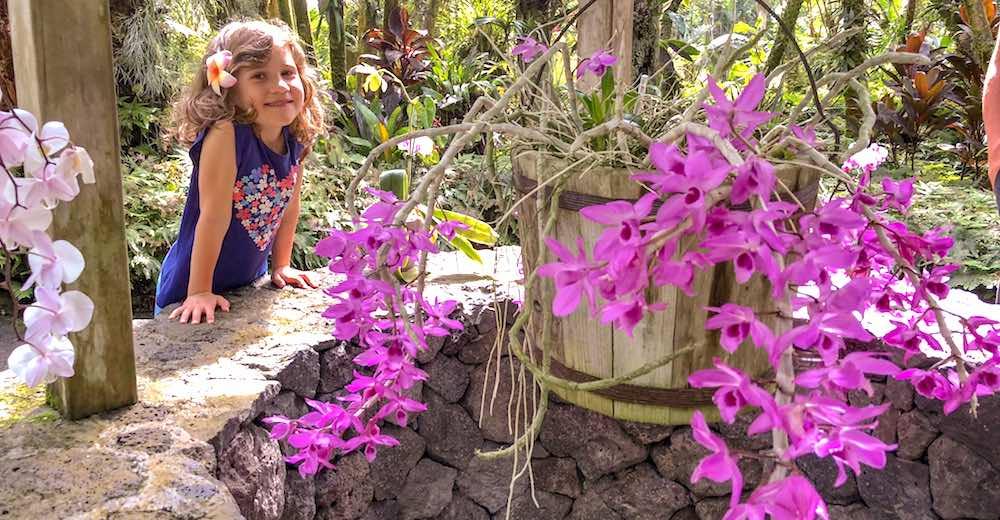 Kleine meid bij de waterput en orchideeën in de Hawaii Tropical Botanical Gardens in Onomea Bay nabij Hilo, een must tijdens elke reis naar Hawaii