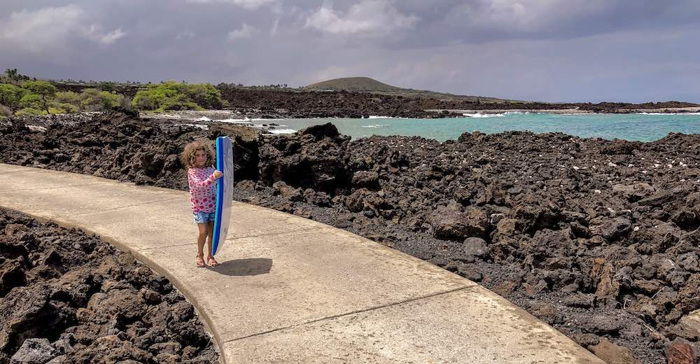 Little girl holding a boogie board while walking on the winding pathway leading from the parking to Kika'ua Point Beach Park