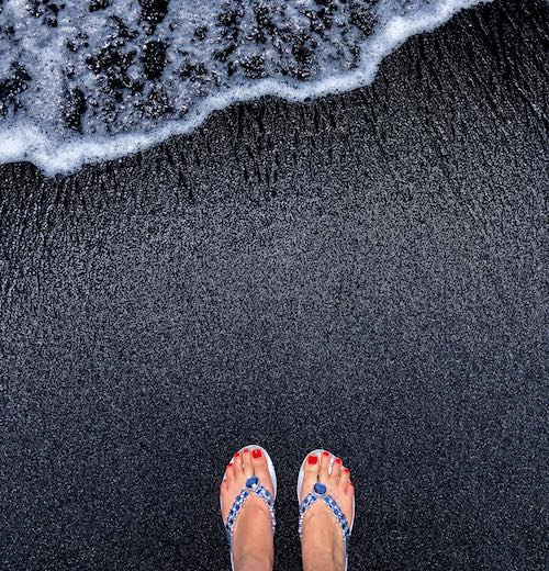 Sparkling flipflops on sparkling black sand beach Punaluʻu in Big Island Hawaii