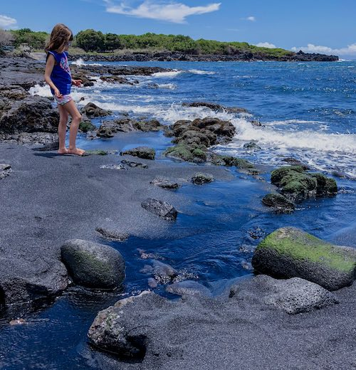 Girl standing on Punaluʻu black sand beach in Hawaii, one of the best Big Island beaches