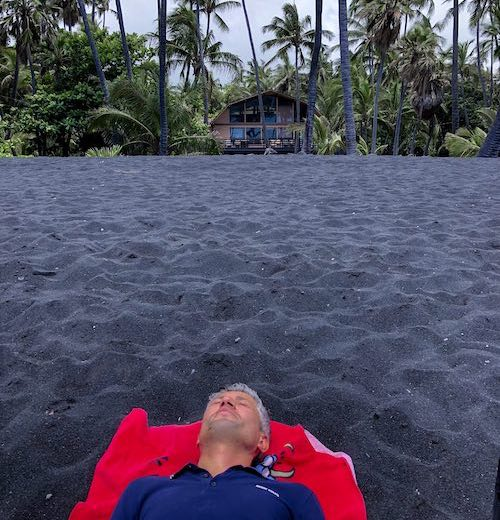CosmopoliDad lounging on Punaluʻu black sand beach on Hawaii Big Island