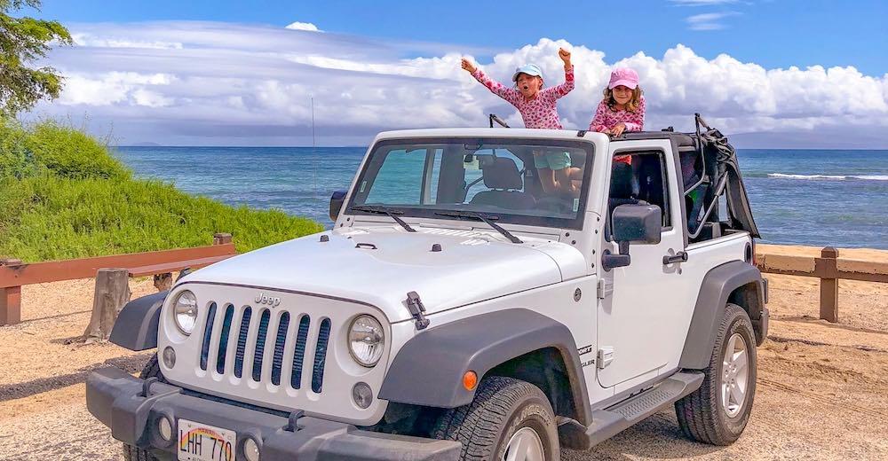 Twee meisjes juichen in hun open jeep tijdens een road trip als onderdeel van de Hawaii vakantie