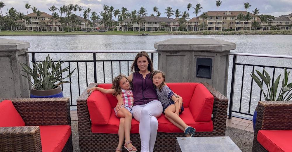 CosmopoliMom Sarah and her daughters sitting in a red sofa at Waikoloa Village, one of the best places to stay on Big Island Hawaii