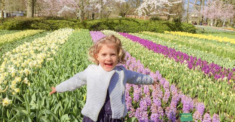Little girl enjoying the tulip fields in Holland's famous Keukenhof Gardens