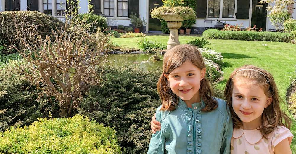 Two little sisters smiling in the courtyard of the Hofje van Bakenes, the oldest hofje of Haarlem in the Netherlands